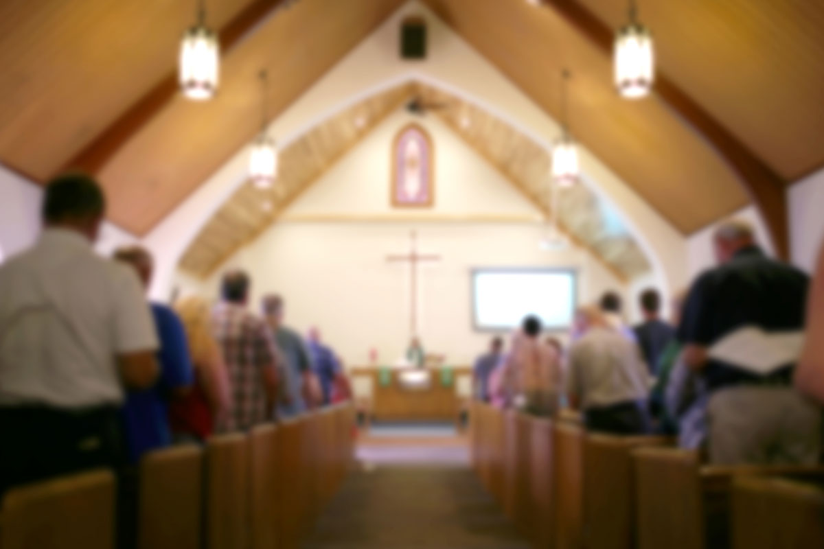 A blurred photo of the inside of a church sanctuary that is filled with people in the pews, and the pastor stands under a large cross at the altar.