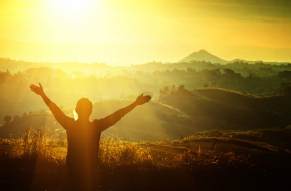 Man standing in a sunlit field with his arms raised